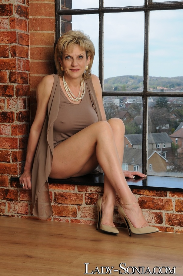 Blonde Bimbo In Grey Dress And Gold Earrings Poses In ...