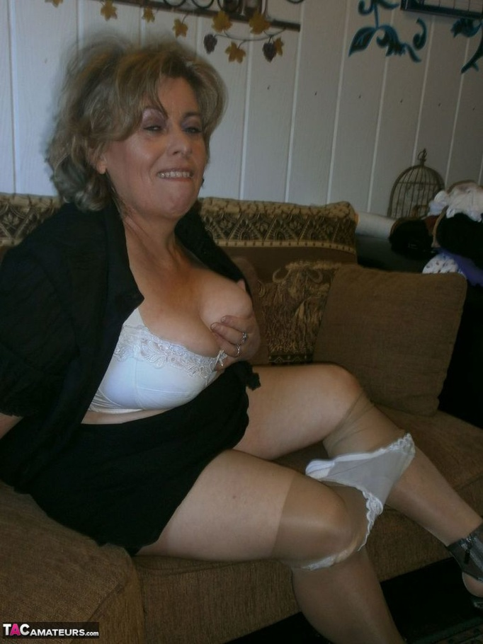 Voluptuous blonde MILF shows her large tits to the cam and poses in nylon  pantyhose -