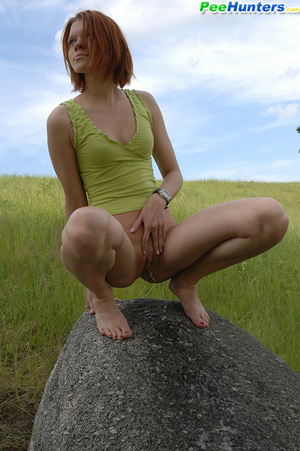 Babe tinkles on a rock in the middle of a field - XXXonXXX - Pic 1
