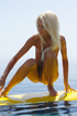 Blonde teen chick posing on a yellows surf board…