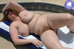 Big breasted redhead sunbathing by the p - XXX Dessert - Picture 3