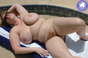 Big breasted redhead sunbathing by the p - XXX Dessert - Picture 4