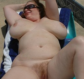 Big breasted redhead sunbathing by the pool