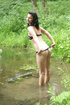 Naked brunette teen girl posing in a small forest…