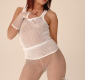 Lovely chick in a white fishnet vest, transparent tights and high boots
