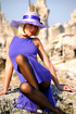 Bodacious blonde lady in a blue dress and a hat posing in black tights