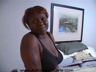 Ponytailed ebony grandmother shows off her big tits and - Picture 1