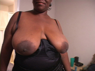 Big black mom in a black suit shows off her huge titties - Picture 3