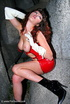 Brunette in red latex minidress performs seductive striptease