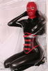 Sexy brunette in black latex jumpsuit takes on red mask