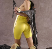 Masked girl in yellow latex comes out of a black sack and reveals her