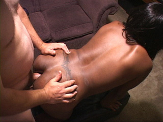 Black ebony bends low on small leather stool to get her - Picture 1