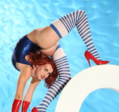 Ginger flexible girl in red latex gloves and shoes…