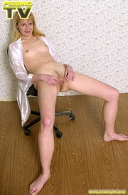 Naked blonde slut sits on a swivel chair while she takes delight in squirting warm golden pee all over the floor and on her feet