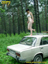 Half naked teen walks on a ladder proped on two cars squats and relieves