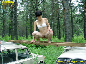 Daring brunette teen balances on a ladder proped on two cars, squats and relieves herself right there with out caring as to who is watching her - XXXonXXX - Pic 11