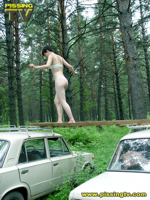 Daring brunette teen balances on a ladder proped on two cars, squats and relieves herself right there with out caring as to who is watching her - XXXonXXX - Pic 17