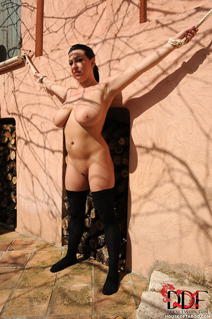 Very busty brunette beauty is tied spread eagled outdoors along the wall of a house and had no qualms about pissing right there - XXXonXXX - Pic 2