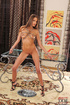Naked brown hared beauty is chained standing on…