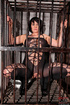 Short haired brunette slave wearing a fishnet body suit is kept inside