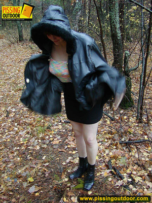 Shy teen wrapped up in a hooded black coat bends down to piss freely in the woods - XXXonXXX - Pic 1