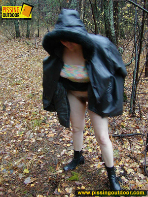 Shy teen wrapped up in a hooded black coat bends down to piss freely in the woods - XXXonXXX - Pic 2