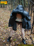 Shy teen wrapped up in a hooded black coat bends down to piss freely in