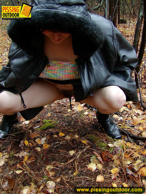 Shy teen wrapped up in a hooded black coat bends down to piss freely in the woods - XXXonXXX - Pic 7