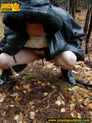 Shy teen wrapped up in a hooded black coat bends down to piss freely in the woods - XXXonXXX - Pic 8