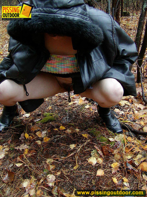 Shy teen wrapped up in a hooded black coat bends down to piss freely in the woods - XXXonXXX - Pic 10