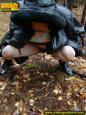 Shy teen wrapped up in a hooded black coat bends down to piss freely in the woods - XXXonXXX - Pic 13