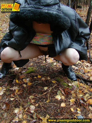 Shy teen wrapped up in a hooded black coat bends down to piss freely in the woods - XXXonXXX - Pic 14
