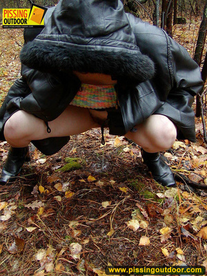 Shy teen wrapped up in a hooded black coat bends down to piss freely in the woods - XXXonXXX - Pic 16