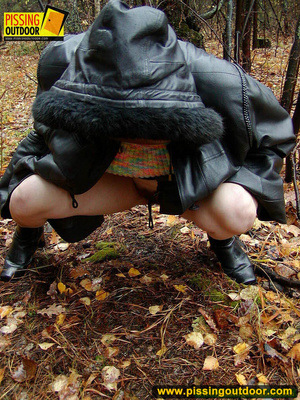 Shy teen wrapped up in a hooded black coat bends down to piss freely in the woods - XXXonXXX - Pic 18