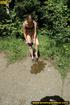 Lady in bikini removes panty along walkway in forest to piss in public