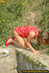 Lady in red with hot small tits hangs up on stone…