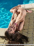 Sultry little sexpot sits poolside with her gaping vag