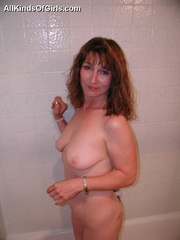 Big boobed slim granny slowly undressing in front of a - Picture 2