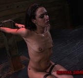 Skinny brunette girl roped to a column can't…