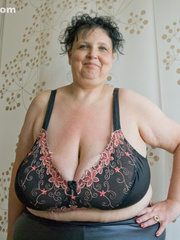 Curly brunette mature demonstrates her enormous boobs - Picture 2