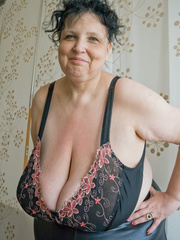 Curly brunette mature demonstrates her enormous boobs - Picture 3