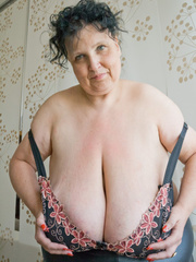 Curly brunette mature demonstrates her enormous boobs - Picture 12
