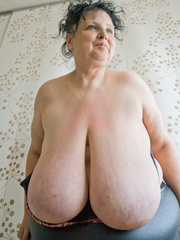 Curly brunette mature demonstrates her enormous boobs - Picture 14