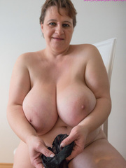 Big-titted MILF putting on black stockings to look - Picture 1