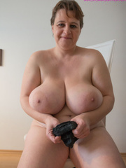 Big-titted MILF putting on black stockings to look - Picture 2