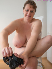 Big-titted MILF putting on black stockings to look - Picture 3