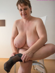 Big-titted MILF putting on black stockings to look - Picture 4