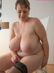 Big-titted MILF putting on black stockings to look - Picture 9