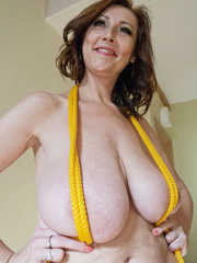 Busty goddess topless having fun with a yellow rope - Picture 5