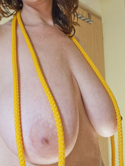 Busty goddess topless having fun with a yellow rope - Picture 6